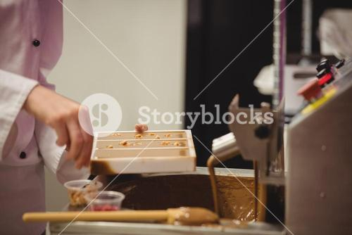 Worker sprinkling confectionary on chocolate mould