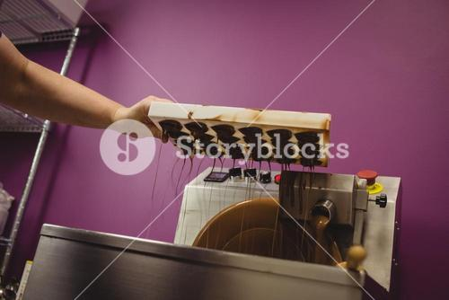 Worker pouring melted chocolate in blending machine