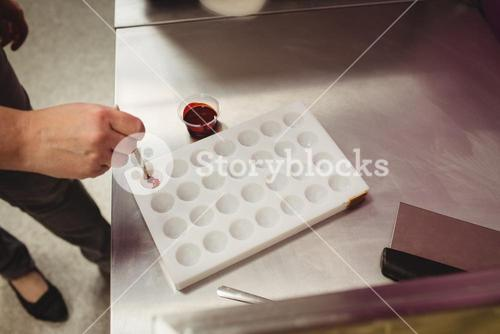 Worker painting a chocolate mould using colored chocolate