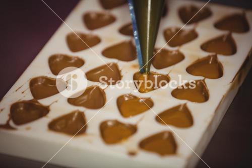 Filling a chocolate mould with a piping bag
