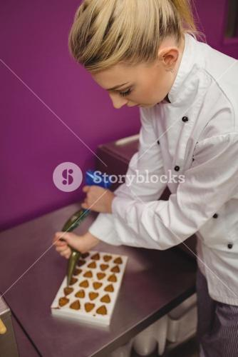 Worker filling mould with piping bag