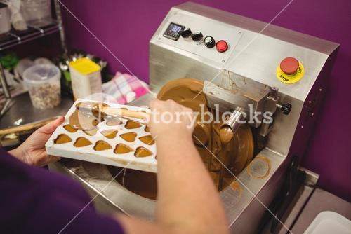Worker filling mould with melted chocolate