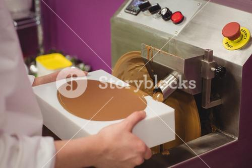 Mid section of worker filling mould with melted chocolate