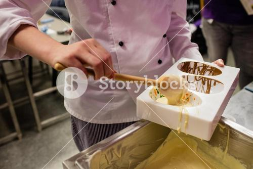 Mid section of worker filling chocolate mould