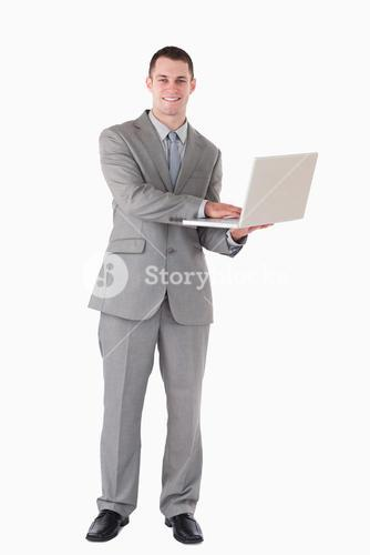 Portrait of a young businessman holding a laptop