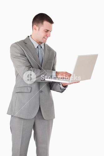 Portrait of a young businessman working with a laptop