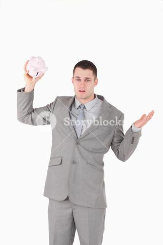 Portrait of a broke businessman shaking an empty piggy bank