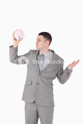 Portrait of a broke businessman looking at an empty piggy bank