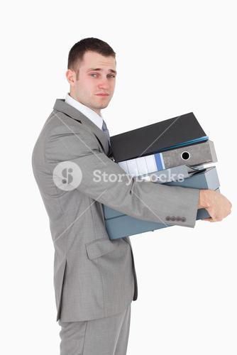 Portrait of a stressed businessman holding a stack of binders