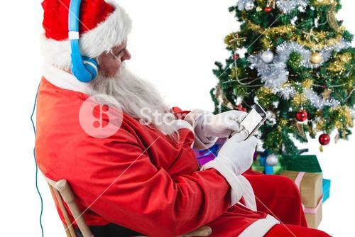 Santa claus using a mobile phone with christmas tree and gifts