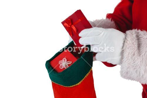 Santa claus putting presents in christmas stockings