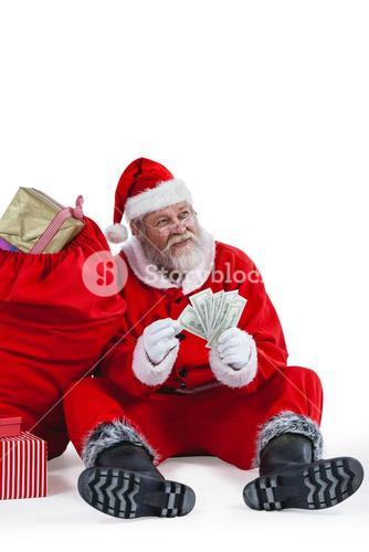 Santa claus sitting next to gift counting a currency note