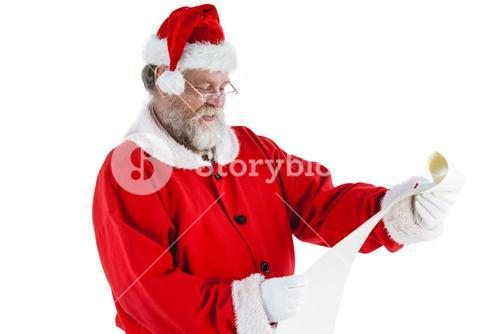 Santa claus smiling and reading a scroll