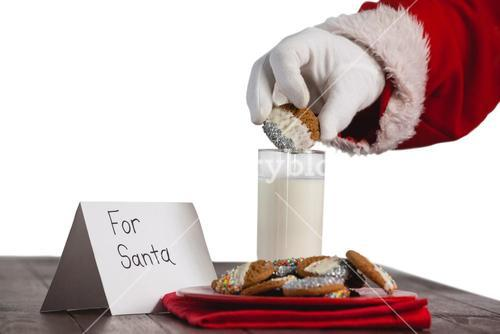 Close-up of santa claus dipping cookies in a glass of milk