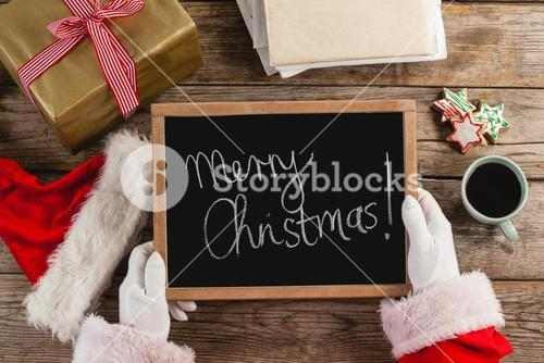 Santa claus holding a slate with merry christmas text
