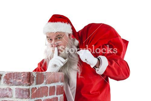 Santa claus with finger on lips standing beside chimney
