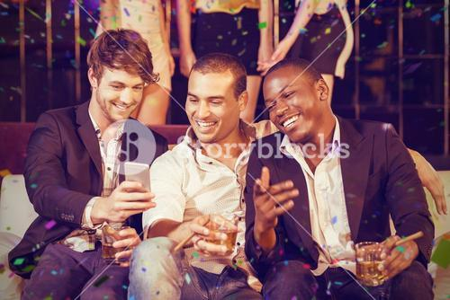Composite image of happy friends using smartphone while sitting on sofa