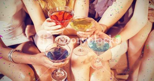 Composite image of girls with cocktails toasting