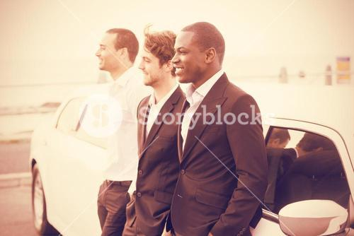 Side view of men posing next to limousine