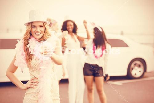 Women holding champagne next to limousine