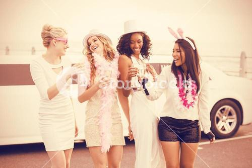 Female friends holding champagne while standing