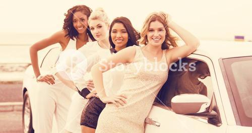 Portrait of cheerful female friends posing while leaning on limousine