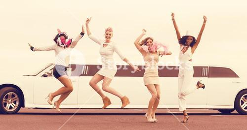 Happy friends jumping in front of limousine