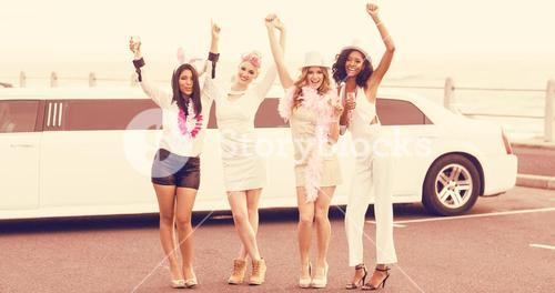 Cheerful friends with arms raised dancing in front of limousine
