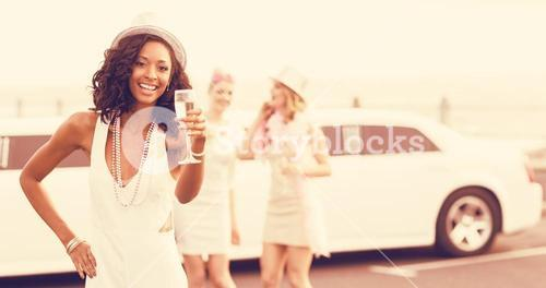 Portrait of women holding champagne next to limousine