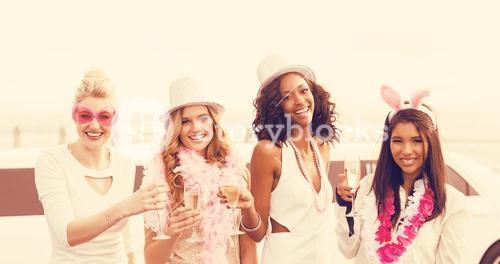 Portrait of women holding champagne flute while standing