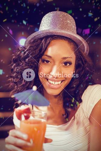 Composite image of pretty girl with cocktail and glitter hat