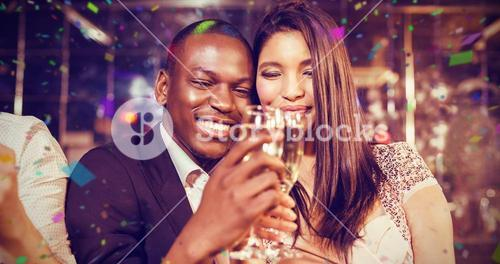 Composite image of happy friends toasting with champagne
