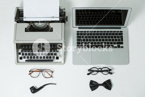Typewriter and laptop with spectacles, smoking pipe and bow