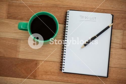 Close-up of coffee mug with diary and pen