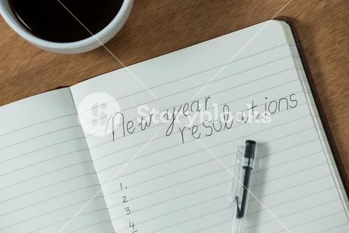 New year resolutions written on diary with coffee mug