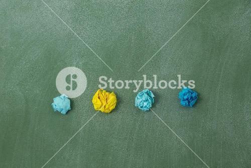 Colorful crumpled paper on a green background