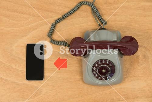 Mobile phone and vintage telephone on wooden table