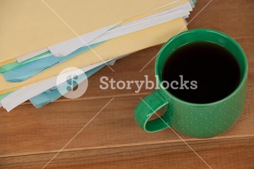 Files and coffee mug on wooden desk