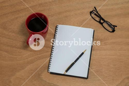 Coffee mug with blank diary, pen and spectacles