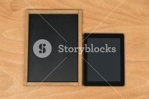 Chalk board and digital tablet on wooden background