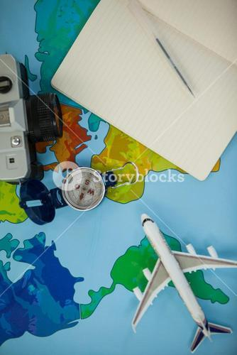 Digital camera, dairy, pen, map, compass and airplane model on table