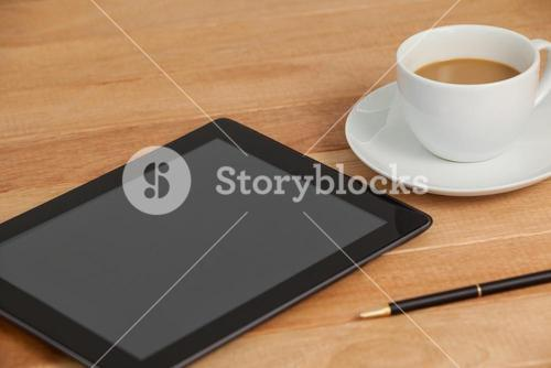 Digital tablet with pen and cup of tea