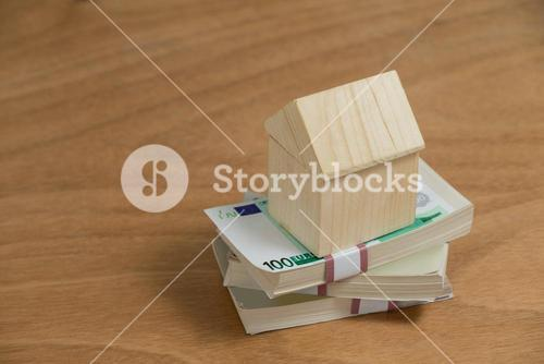 Model house on a pile of money