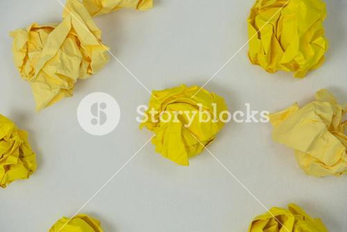Yellow crumpled paper balls on a white background