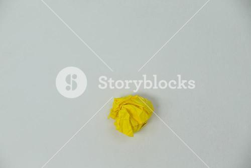 Yellow crumpled paper ball on a white background