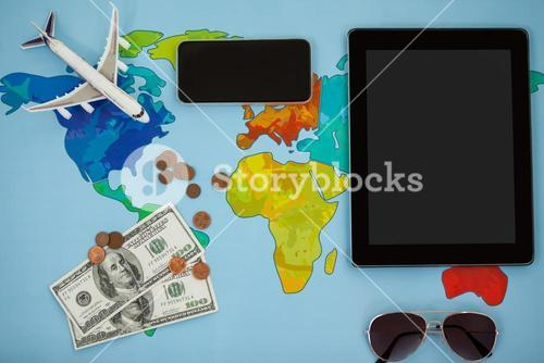 Electronic gadgets, sunglasses, dollar and airplane model
