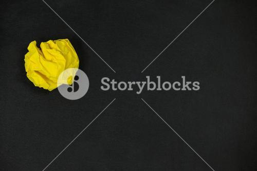 Yellow crumpled paper ball on a black background