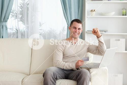 Happy man shopping online with the fist up