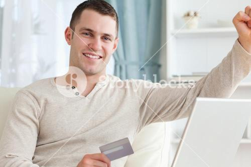 Smiling man shopping online with the fist up
