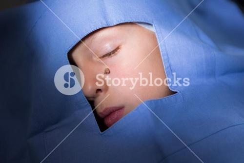 Close-up of unconscious patient with mole on chick